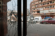 Sunni neighborhood Bab al-Tebbaneh. Syria Street. Bullet holes in shop windows, these shots are from the Sunni side and were fired during street fighting. The building on the other side is riddled with bullets and RPG missiles: these shots are of Alawi origine...Quartier sunnite Bab al-Tebbaneh. Rue de Syrie. Traces de balles dans boutique  ces tirs viennent du côté sunnite et ont été tirés lors des combats de rue. La façade en face est criblée de balles et projectiles RPG : ces tirs sont d'origine alaouite.