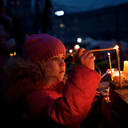 KIEV, UKRAINE - February 23, 2014: A little girl lights candles in memory of the anti-government protestors killed during violent clashes with Ukrainian special forces, in Kiev's Independence Square. CREDIT: Paulo Nunes dos Santos