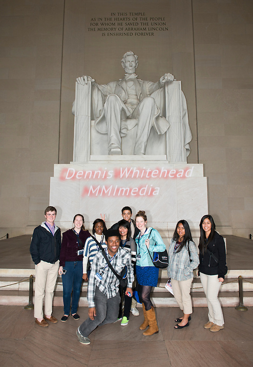 High school students pose in front of the statue of Abraham Lincoln inside the Lincoln Memorial, a popular tourist destination in Washington, DC.