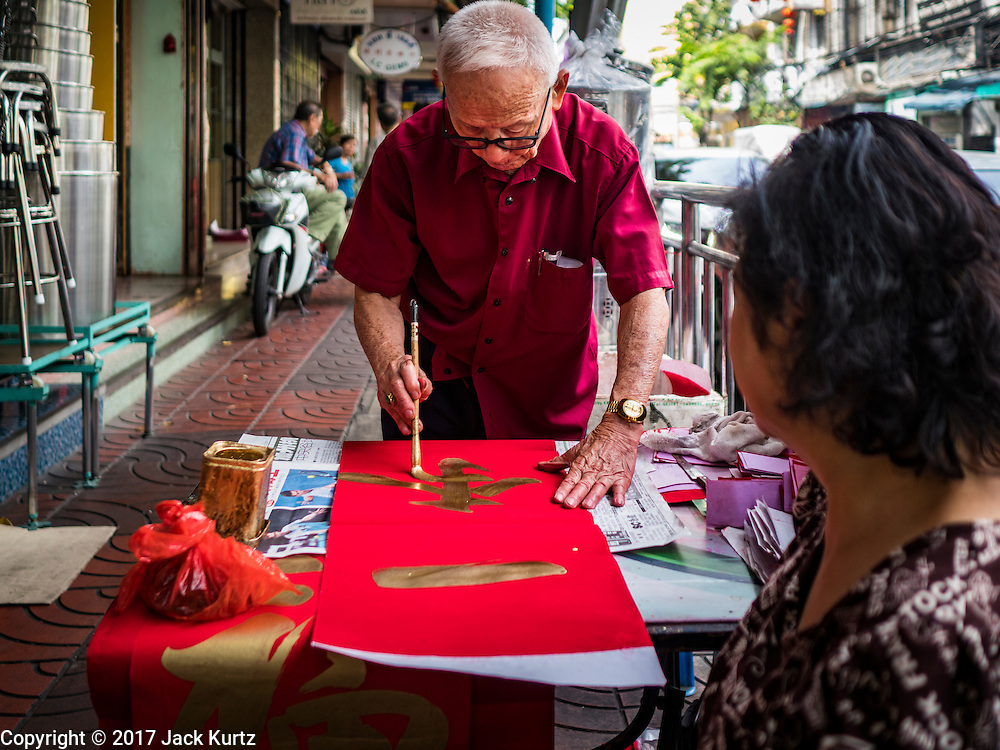 """18 JANUARY 2017 - BANGKOK, THAILAND: A woman watches a traditional Chinese calligrapher write out New Years greetings in Bangkok's Chinatown district, before the celebration of the Lunar New Year. Chinese New Year, also called Lunar New Year or Tet (in Vietnamese communities) starts Saturday, 28 January. The coming year will be the """"Year of the Rooster."""" Thailand has the largest overseas Chinese population in the world; about 14 percent of Thais are of Chinese ancestry and some Chinese holidays, especially Chinese New Year, are widely celebrated in Thailand.       PHOTO BY JACK KURTZ"""