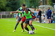 AFC Wimbledon defender Nesta Guiness-Walker (18) challenged by Hampton & Richmond forward Cole Brown during the Pre-Season Friendly match between Hampton & Richmond and AFC Wimbledon at Beveree Stadium, Richmond Upon Thames, United Kingdom on 27 July 2019.