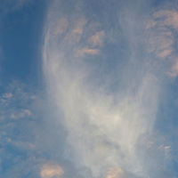 The lower portion of the cloud looks life a face falling to earth and losing its form to speed and the billowing of clouds dissipate above.