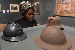 "© Licensed to London News Pictures. 04/06/2018. LONDON, UK. A gallery staff member views (L to R) ""French, British and German helmets"", 1916-18, at a preview of ""Aftermath:  Art in the wake of World War One"" at Tate Britain.  The exhibition marks 100 years since the end of the First World War, exploring the impact of the conflict on British, German, and French art in over 150 works from 1916 to 1932.  The show runs 5 June to 23 September 2018.  Photo credit: Stephen Chung/LNP"