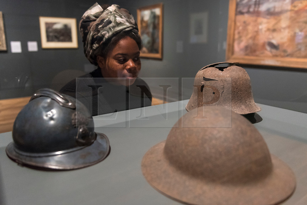 """© Licensed to London News Pictures. 04/06/2018. LONDON, UK. A gallery staff member views (L to R) """"French, British and German helmets"""", 1916-18, at a preview of """"Aftermath:  Art in the wake of World War One"""" at Tate Britain.  The exhibition marks 100 years since the end of the First World War, exploring the impact of the conflict on British, German, and French art in over 150 works from 1916 to 1932.  The show runs 5 June to 23 September 2018.  Photo credit: Stephen Chung/LNP"""