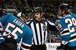 March 19, 2011; San Jose, CA, USA;  NHL linesman Lonnie Cameron (center) separates San Jose Sharks left wing Ben Eager (55) and right wing Ryane Clowe (29) from St. Louis Blues players during the first period at HP Pavilion. Mandatory Credit: Jason O. Watson / US PRESSWIRE