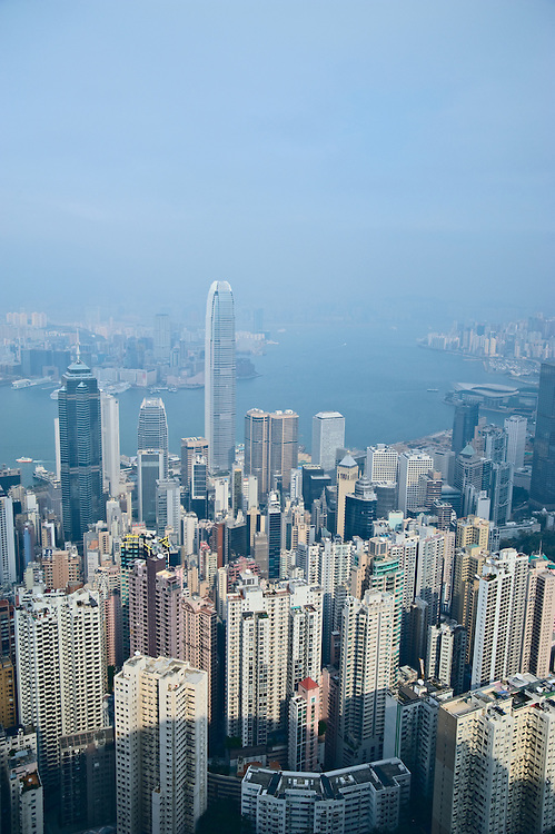 Office towers and apartment buildings of Hong Kong from The Peak, with Victoria Harbour and Kowloon visible through haze in distance