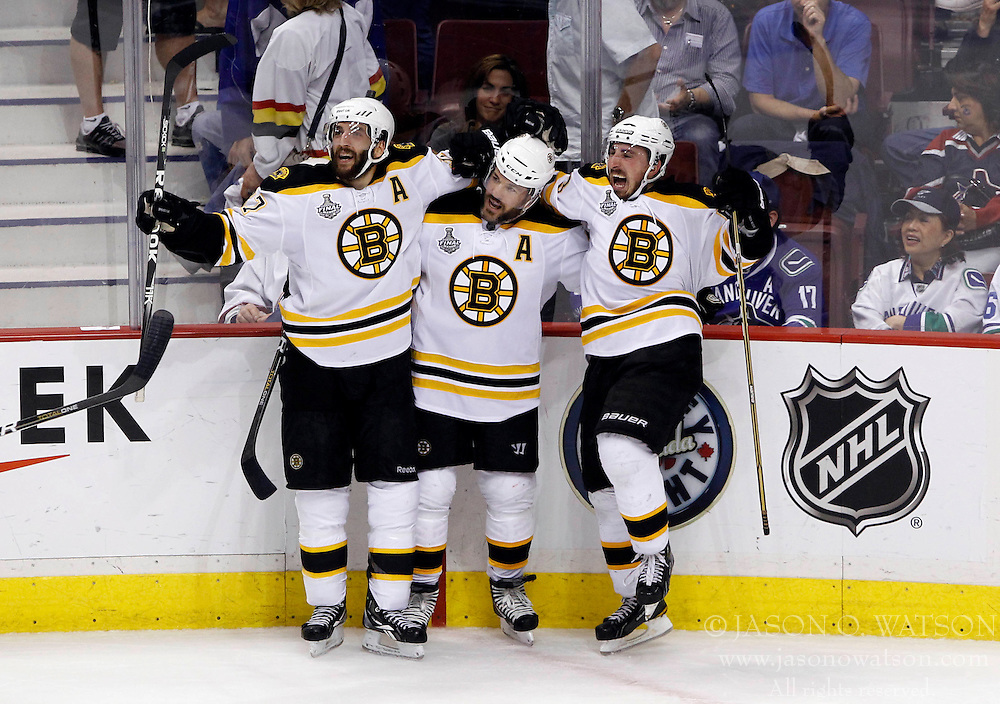 June 15, 2011; Vancouver, BC, CANADA; Boston Bruins left wing Brad Marchand (right) celebrates with left wing Mark Recchi (middle) and center Patrice Bergeron (left) after scoring an empty-net goal in the third period in game seven of the 2011 Stanley Cup Finals at Rogers Arena. The Bruins won 4-0 to win the Stanley Cup. Mandatory Credit: Jason O. Watson / US PRESSWIRE
