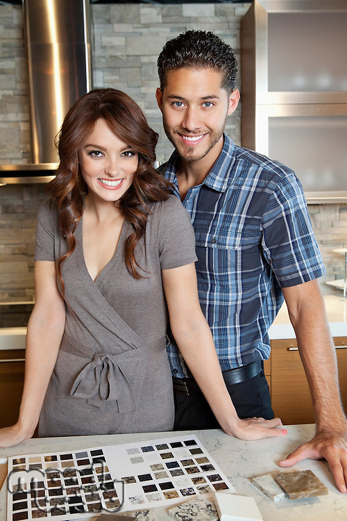 Portrait of beautiful young couple standing in model home kitchen with tile color samples