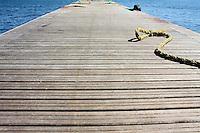 Pontile di legno sulla banchina del lungomare di Taranto in città vecchia e cima gialla di un peschereccio.