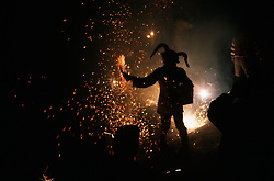 Man wearing costume holding fireworks at carnival in Toledo,