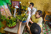 04 JUNE 2014 - YANGON, YANGON REGION, MYANMAR: People pray to a deity for good luck in Botataung Paya (Pagoda) in Yangon, Myanmar (Rangoon, Burma). Botataung is one of the most famous pagodas in Yangon with maze like interior of gold leaf covered walls. The pagoda houses a hair from the Buddha and is one of the most sacred sites in Burma. Yangon, with a population of over five million, continues to be the country's largest city and the most important commercial center.     PHOTO BY JACK KURTZ
