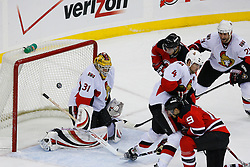 Jan 4, 2008; Newark, NJ, USA; Ottawa Senators goalie Alex Auld (31) makes a save on New Jersey Devils center Travis Zajac (19) during the third period at the Prudential Center. The Devils defeated the Senators 4-3 in overtime.
