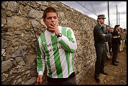 Podes, Asturias,Spain<br /> Football field in Podes, a small village in the north of Spain.A fan is smoking while the game is played. &copy; Carmen Secanella.