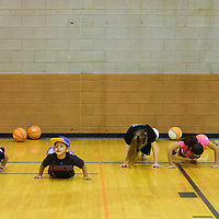 Children attempt to do push ups during a basketball camp hosted at Gallup High School on June 7, 2017.