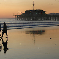 A couple walk hand-in-hand along Santa Monica Beach amid the sunset.
