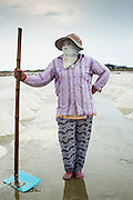 24 APRIL 2013 - SAMUT SONGKHRAM, SAMUT SONGKHRAM, THAILAND: A worker in the salt fields near Samut Songkhram, Thailand. Even though it's very hot and humid, workers cover themselves from head to toe for protection from the sun. The 2013 salt harvest in Thailand and Cambodia has been impacted by unseasonably heavy rains. Normally, the salt fields are prepped for in December, January and February, when they're leveled and flooded with sea water. Salt is harvested from the fields from late February through May, as the water evaporates leaving salt behind. This year rains in December and January limited access to the fields and rain again in March and April has reduced the amount of salt available in the fields. Thai salt farmers are finishing the harvest as best they can, but the harvest in neighboring Cambodia ended 6 weeks early because of rain. Salt has traditionally been harvested in tidal basins along the coast southwest of Bangkok but industrial development in the area has reduced the amount of land available for commercial salt production and now salt is mainly harvested in a small part of Samut Songkhram province.      PHOTO BY JACK KURTZ
