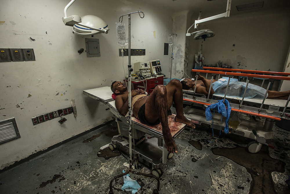 BARCELONA, VENEZUELA - APRIL 16, 2016:  Jose Villarroel, 25, waited covered in his own blood, for hours in the emergency operating room of Hospital Universitario Dr. Luís Razetti, for doctors to operate on him after he was stabbed in the abdomen. The hospital doesn't have the equipment to scan his abdomen, and told Mr. Villarroel that he would have to figure out a way to  arrange for a private ambulance to take him to a private clinic, get the needed scan done there, and bring it back to them before they could operate. Hospital Razetti (as it is called for short) is one of the worst state-run, public hospitals in Venezuela.  Doctors compare it to working in a war zone - they regularly have to turn patients away, because they don't have the majority of medicines  or medical equipment and supplies needed to give them medical attention.  When they do accept patients, they have to work with extremely limited resources, because they don't have the supplies they need for things like X-Rays,  and many exams nd operations.  The hospital's infrastructure is crumbling, and staff don't have all the cleaning supplies required to keep the hospital sanitary. The hospital also suffers from weekly shortages of running water and electricity.  In April, several babies died when a power outage turned off the incubators, and the hospital's generator failed to work because of lack of maintenance.  The same month, authorities found over 100 pieces of medical equipment, stolen from the hospital in the home of the assistant to the hospital's director.  Despite having the largest oil reserves in the world, falling oil prices and wide-spread government corruption have pushed Venezuela into an economic crisis, with the highest inflation in the world and chronic shortages of food and medical supplies. PHOTO: Meridith Kohut