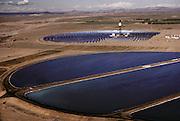 Solar energy electrical generating power plant in the Mojave Desert near Barstow, California. Solar One consists of a circular arrangement of 1, 818 mirrors, each measuring 23x23 feet (7x7 meters). These mirrors focus the sunlight onto a huge central receiver, which sits atop a 300-foot (91 meter) tower. (1985).