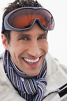 Man wearing ski goggles smiling portrait close up