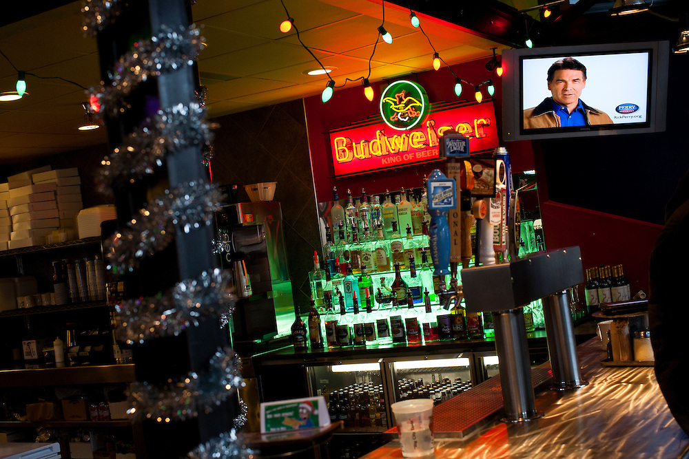 A television advertisement for Republican presidential candidate Rick Perry plays at Doughy Joey's Pizza before a Perry campaign event at the restaurant on Friday, December 30, 2011 in Waterloo, IA.