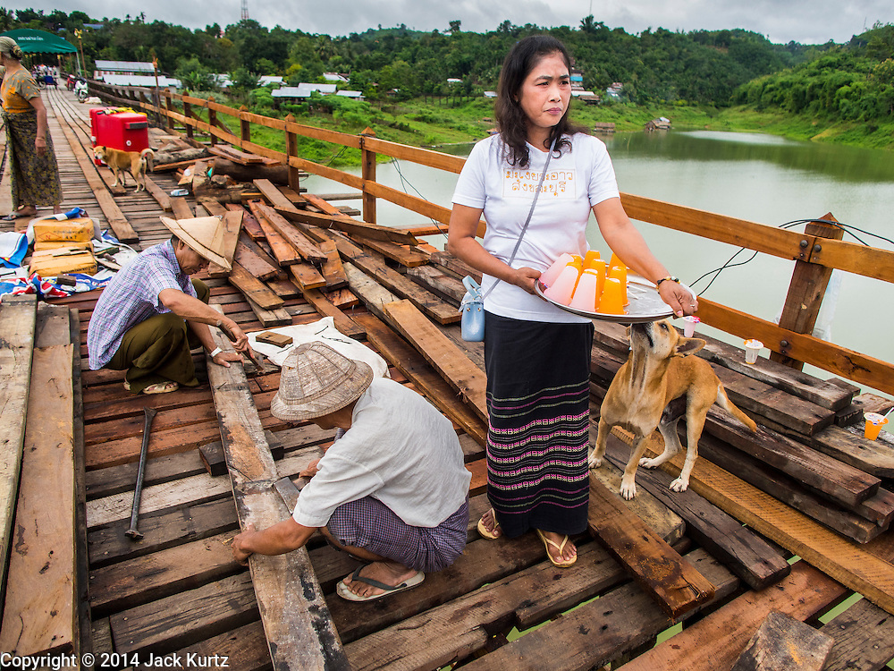 17 SEPTEMBER 2014 - SANGKHLA BURI, KANCHANABURI, THAILAND: A member of the Mon community brings fruit juice to workers rebuilding the Mon Bridge in Sangkhla Buri. The 2800 foot long (850 meters) Saphan Mon (Mon Bridge) spans the Song Kalia River. It is reportedly second longest wooden bridge in the world. The bridge was severely damaged during heavy rainfall in July 2013 when its 230 foot middle section  (70 meters) collapsed during flooding. Officially known as Uttamanusorn Bridge, the bridge has been used by people in Sangkhla Buri (also known as Sangkhlaburi) for 20 years. The bridge was was conceived by Luang Pho Uttama, the late abbot of of Wat Wang Wiwekaram, and was built by hand by Mon refugees from Myanmar (then Burma). The wooden bridge is one of the leading tourist attractions in Kanchanaburi province. The loss of the bridge has hurt the economy of the Mon community opposite Sangkhla Buri. The repair has taken far longer than expected. Thai Prime Minister General Prayuth Chan-ocha ordered an engineer unit of the Royal Thai Army to help the local Mon population repair the bridge. Local people said they hope the bridge is repaired by the end November, which is when the tourist season starts.    PHOTO BY JACK KURTZ