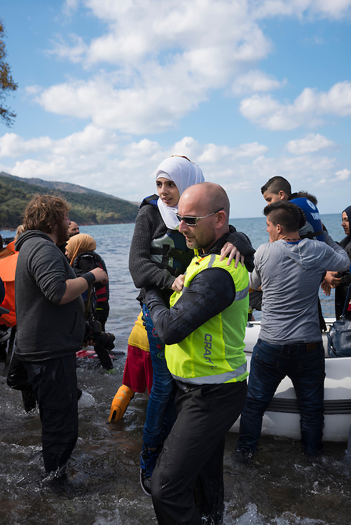 A Norwegian volunteer on the Greek island of Lesbos carries an Arab girl to shore from the rubber dingy she and other migrants had traveled in from Turkey, 10 kilometers away.