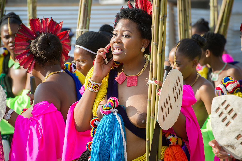Ludzidzini, Swaziland, Africa - Annual Umhlanga, or reed dance ceremony, in which up to 100,000 young Swazi women gather to celebrate their virginity and honor the queen mother during the 8 day long event.<br /> Maiden using cell phone