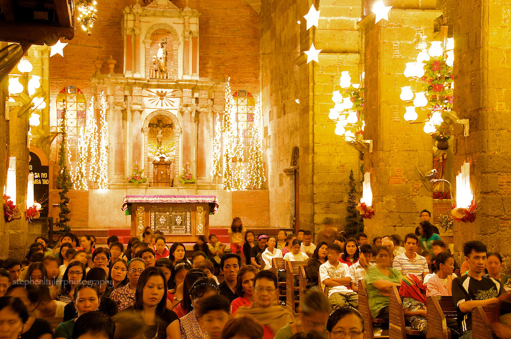 Followers gather inside of St Joseph's Church of the Bamboo Organ in Las Pinas during Simbang Gabi, where nine straight nights of Mass is celebrated at 4 AM and leads up to a Midnight Mass on Christmas eve.