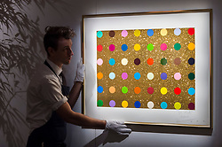 "© Licensed to London News Pictures. 25/10/2019. LONDON, UK. A technician presents ""Untitled (Gold gift spot)"", 2008, by Damien Hirst (Est. GBP5-7k). Preview of ""GOLD: The Midas Touch"" at Sotheby's in New Bond Street.  Artworks spanning six centuries dedicated to gold will be offered for sale on 29 October.  Photo credit: Stephen Chung/LNP"