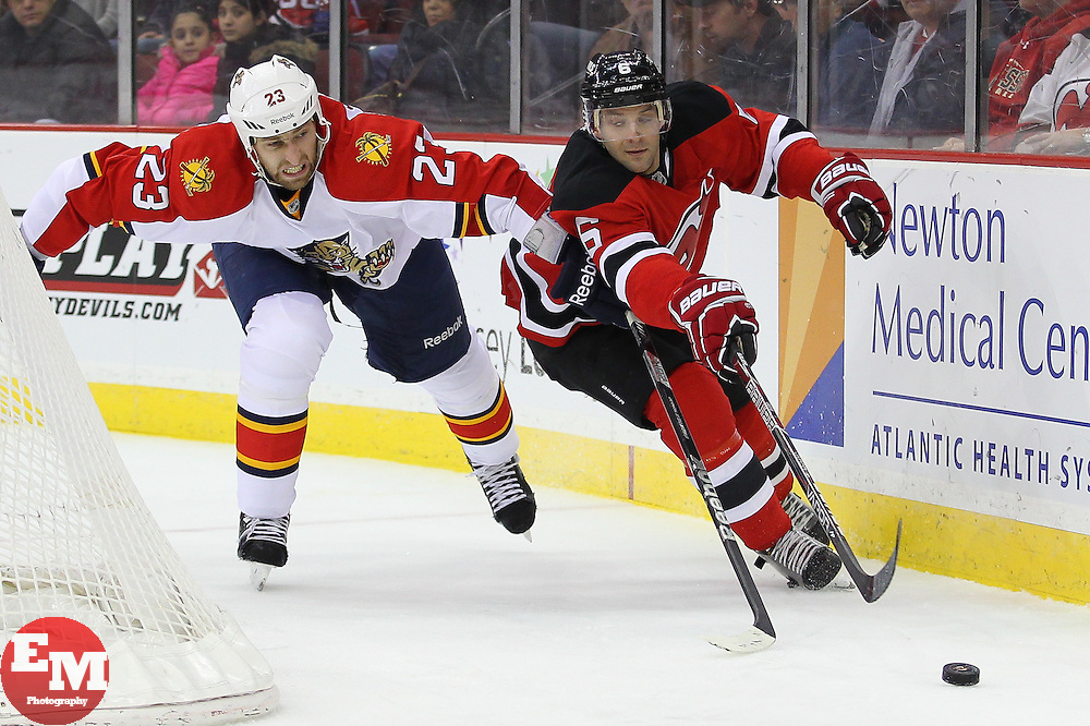 Mar 23, 2013; Newark, NJ, USA; New Jersey Devils defenseman Andy Greene (6) and Florida Panthers defenseman Tyson Strachan (23) chase the puck during the third period at the Prudential Center. The Devils defeated the Panthers 2-1.