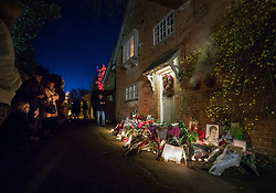 © Licensed to London News Pictures. 26/12/2016. Goring-, UK. Fans (L) look at tributes to George Michael placed at the front door of his house in Goring. Pop superstar George Michael died on Christmas day at his Oxfordshire home on the River Thames aged 53. Photo credit: Peter Macdiarmid/LNP