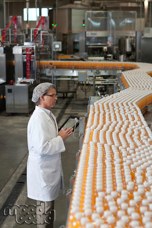 Man inspecting orange juice bottles at bottling plant