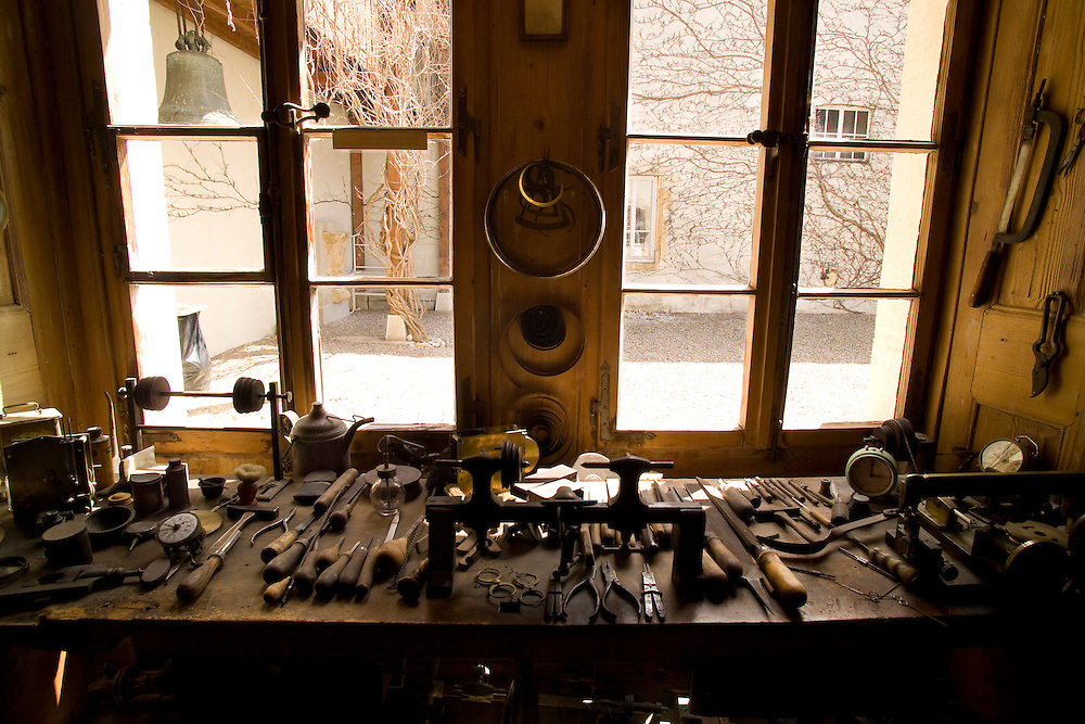 19th Century Watchmaker's workbench covered with tools of the trade in front of a window looking on to the street with bare limbed tree's reaching across view with a bell outside window on the left. Coil of three different sizes hanging on wall with other tools hanging on other wood panel around workbench. Multiple clocks, or timepieces on bench with a tea pot in front of window on left.