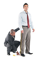 Tailor taking measure leg of customer