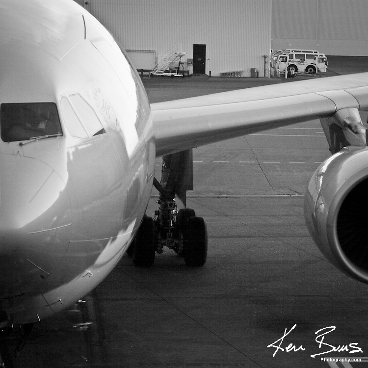 A black and white image of a Northwest Airlines Boeing 767 at a gate in Seattle Tacoma Airport