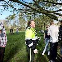 Nederland, amsterdam , 8 april 2011..Milieuwacht van amsterdam in het Vondelpark..Stadsdeel Zuid stuurt dit weekend een schoonmaakteam naar het Vondelpark om te voorkomen dat het Vondelpark opnieuw in een vuilnisbelt verandert..De schoonmakers worden bijgestaan door de vrijwilligers van de Milieuwacht amsterdam..Op de foto een schoonmaker van de milieuwacht stuit op zuipende en rommelmakende scholieren op vrijdagmiddag in het vondelpark..Drinking students in the Vondelpark in Amsterdam, chilling after a week of exams. The Environmental Watch is checking and forcing the youth to clean up the mess.