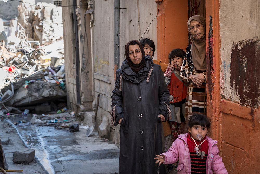 Sawsan (left), her mother Nuhad, and her daughters stand at the entrance to their home in the Old City of Mosul. Their house, which was partially damaged during the fighting between Iraqi forces and ISIS, is surrounded by the ruins of their neighbours' homes that were hit by airstrikes, and the stench of bodies still trapped under the rubble.