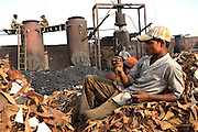 Workers at one of the illegal dumping and burning grounds on the outskirts of Jajmau, near the Ganges River, are portrayed while taking a break on a pile of scrap leather destined to be boiled and reduced to a thin dust: the first process to fertilisers and chicken food, in Kanpur, Uttar Pradesh.