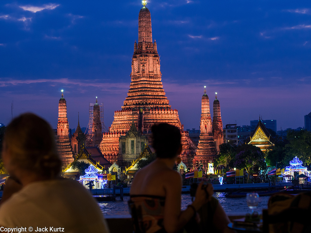 """19 DECEMBER 2013 - BANGKOK, THAILAND:  Wat Arun after the sunset. Wat Arun Ratchawararam Ratchawaramahawihan or Wat Arun (""""Temple of Dawn""""), a Buddhist temple (wat) in Bangkok Yai district of Bangkok, on the Thonburi side of the Chao Phraya River. The temple derives its name from the Hindu god Aruna, often personified as the radiations of the rising sun. Wat Arun is among the best known of Thailand's landmarks and the first light of the morning reflects off the surface of the temple with pearly iridescence. Although the temple had existed since at least the seventeenth century, its distinctive Khmer style prang (spires) were built in the early nineteenth century during the reign of King Rama II.        PHOTO BY JACK KURTZ"""