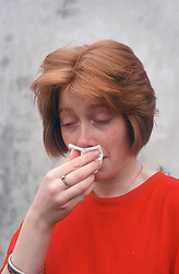 Teenage girl with cold blowing nose on tissue,