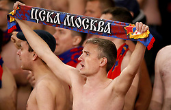 A shirtless CSKA Moscow fans in the stands shows their support by holding up a team scarf during the match