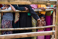 Three-year-old Shehena waits in line with her mom and other Rohingya women for a humanitarian aid distribution at Jamtoli refugee camp in Bangladesh. They are part of what the U.N. has called the world's fastest developing refugee crisis. Hundreds of thousands of Rohingya have fled Myanmar since August. (October 26, 2017)