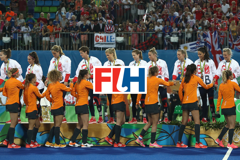 RIO DE JANEIRO, BRAZIL - AUGUST 19:  Team Great Britain are congratulated on the podium by Netherlands after recieving their medals after the Women's Gold Medal Match on Day 14 of the Rio 2016 Olympic Games at the Olympic Hockey Centre on August 19, 2016 in Rio de Janeiro, Brazil.  (Photo by David Rogers/Getty Images)