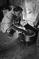 Vera Spein cooks on her Coleman stove at fish camp.  Subsistence activities near the village of Kethluk in southwest Alaska.