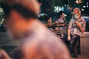 """Pattaya, April 10, 2017 - TomBoy looking at her mobilphone, in front the Oscar Club, The best and most popular place to meet Toms in Pattaya located off Soi Buakhao. When I first entered this place one of the many hot (and handsome) Tomboys giggled while asking me: """"Are you a Adam?"""" That's how they call guys who like Toms here in Thailand.Pattaya, 10 avril 2017 - TomBoy en train de regarder son téléphone portable, devant l'Oscar Club, le meilleur et le plus populaire endroit pour rencontrer des Toms à Pattaya situé au large de Soi Buakhao. Quand je suis entré pour la première fois dans cet endroit, l'un des nombreux Tomboys chauds (et beaux) a gloussé en me le demandant : """"Es-tu un Adam ?"""" C'est comme ça qu'on appelle les gars qui aiment les Toms ici en Thaïlande."""