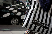 A shopper carrying a striped shopping bag, walks past a car featuring spots in New Bond Street, central London, England.