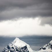 Dark clouds hover above an ice-covered island in the English Strait on the northern Antarctic Peninsula.
