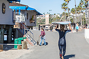 Female Surfer Walking Past Fisherman's Restaurant at the Pier Bowl