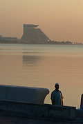 The landmark pyramid of Sheraton Doha hotel at dawn. Muslim coming back from morning prayer at the corniche.