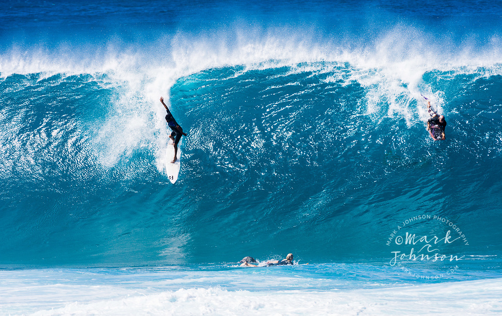 Bodyboarder dropping in on a surfer at the Banzai Pipeline, North Shore, Oahu, Hawaii